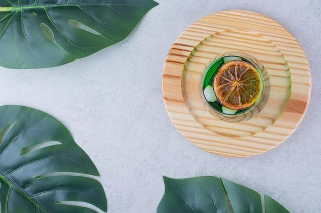 나무 접시에 타라곤 주스의 유리입니다. 고품질 사진