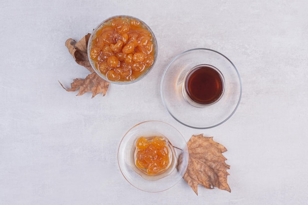白いテーブルの上のお茶とベリージャムのガラス。