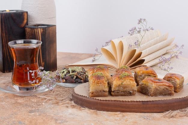 大理石のテーブルにお茶と伝統的な様々なバクラヴァのグラス。