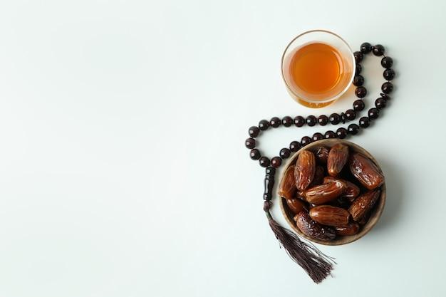 Стакан чая, миска с финиками и четки на белой поверхности