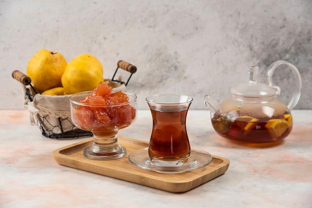 木の板にお茶、ジャム、マルメロの果実のガラス。