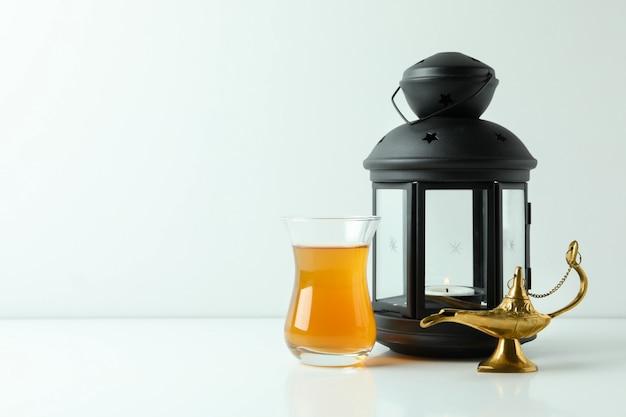 Стакан чая, лампа рамадана и фонарь на белой поверхности