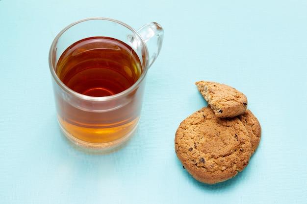 青い背景にクッキーとお茶のグラス