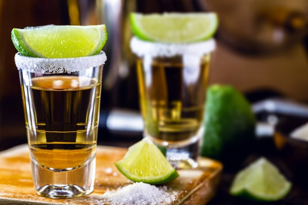 蒸留酒、レモン、塩、青リュウゼツランで作られたメキシコ文化の飲み物、テキーラのグラス。国際テキーラの日。