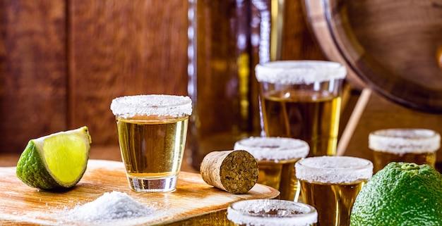 素朴なテーブルの上のテキーラのガラス、レモン、塩、青いリュウゼツランと蒸留酒。国際テキーラデーと7月