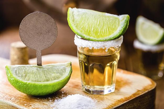 粗い塩、レモン、プレートが付いたテキーラのグラス。価格に余裕があります。プロモーションコンセプト、テキーラデー