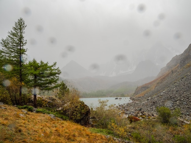 雨のしずくとカメラのガラス。山の湖の雨滴。美しい雨滴。低い雲。曇り空。素晴らしい雰囲気の幽霊のような高原の風景。