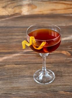 オレンジのツイストを添えたティペラリー カクテルのグラス