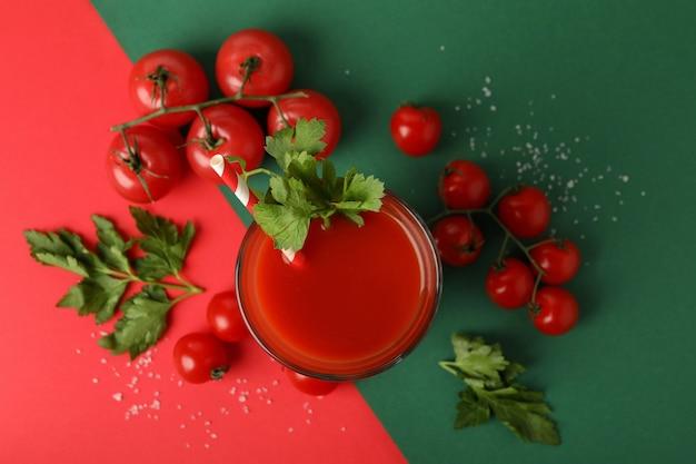 トマトジュースと2トーンの背景にトマトのガラス