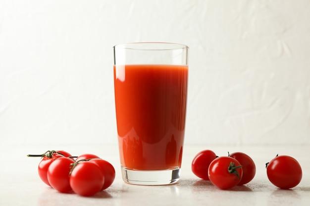 トマトジュースのガラスと白いテクスチャのトマト Premium写真