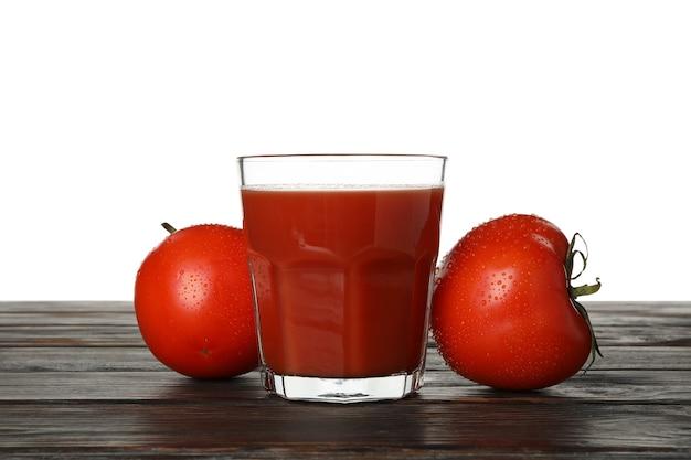 白で隔離される木製のテーブルの上のトマトジュースとトマトのガラス