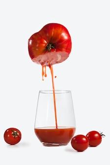 흰색 배경에 창의적으로 촬영된 토마토 주스 한 잔