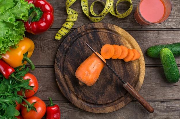 야채와 함께 토마토 주스 한 잔과 나무 테이블 클로즈업에 테이프를 측정합니다. 도마에는 얇게 썬 당근이 있습니다. 공간을 복사합니다. 평면도