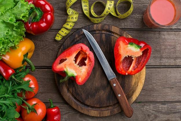 야채와 함께 토마토 주스 한 잔과 나무 테이블 클로즈업에 테이프를 측정합니다. 도마에는 얇게 썬 고추가 있습니다. 공간을 복사합니다. 평면도