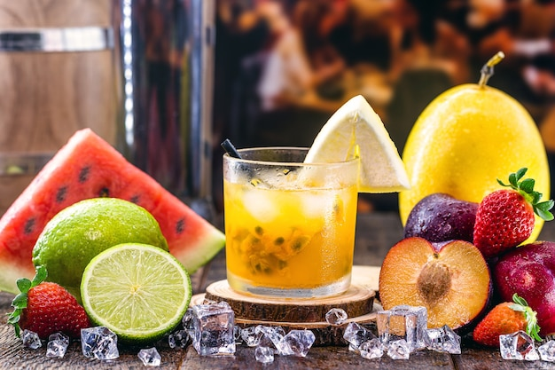 Стакан типичного бразильского напитка под названием кайпиринья, маракуйя, дистиллированный алкоголь, каша и сахар. различные фрукты вокруг