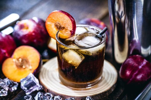 Стакан типичного бразильского напитка под названием кайпиринья, слива, дистиллированный спирт, каша и сахар. различные фрукты вокруг