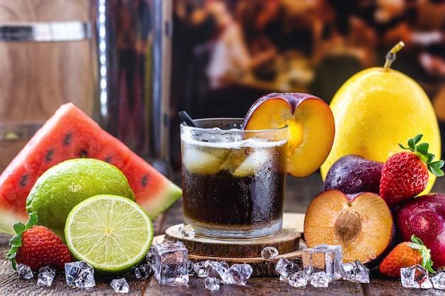 カイピリーニャ、プラム、蒸留アルコール、カシャーサ、砂糖と呼ばれる典型的なブラジルの飲み物のグラス。周りの様々な果物