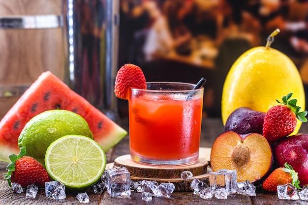 Стакан типичного бразильского напитка под названием кайпиринья, клубника, дистиллированный спирт, каша и сахар. различные фрукты вокруг