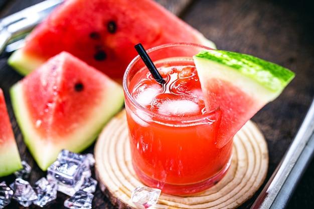 Стакан типичного бразильского напитка под названием кайпиринья, арбуз, дистиллированный спирт, каша и сахар. различные фрукты вокруг