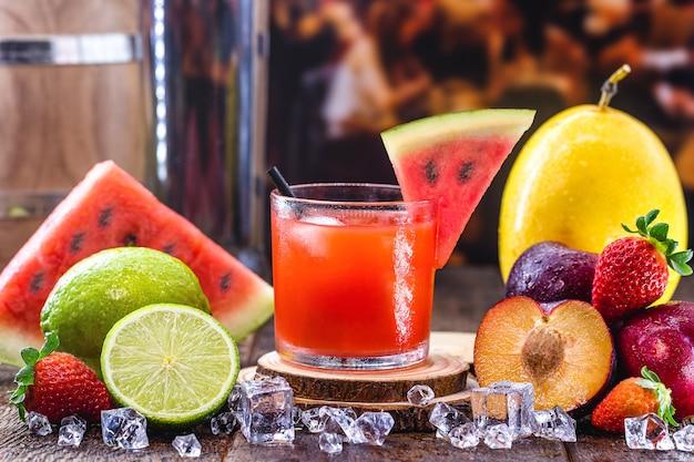 カイピリーニャ、スイカ、蒸留アルコール、カシャーサ、砂糖と呼ばれる典型的なブラジルの飲み物のグラス。周りの様々な果物