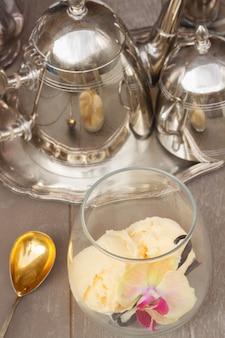 Стакан ванильного мороженого с ложкой