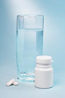 Стакан воды, белая пустая пластиковая бутылка с лекарством и две белые таблетки