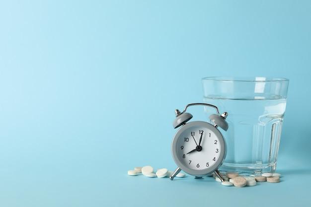 コップ一杯の水、目覚まし時計、青の丸薬