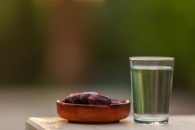 コップ一杯の水とイフタールの乾燥ナツメヤシをイフタールの時間に食べる準備ができているプレートイスラム教とラマダン