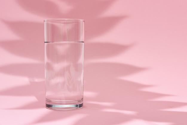 Стакан воды и тени листьев на розовом