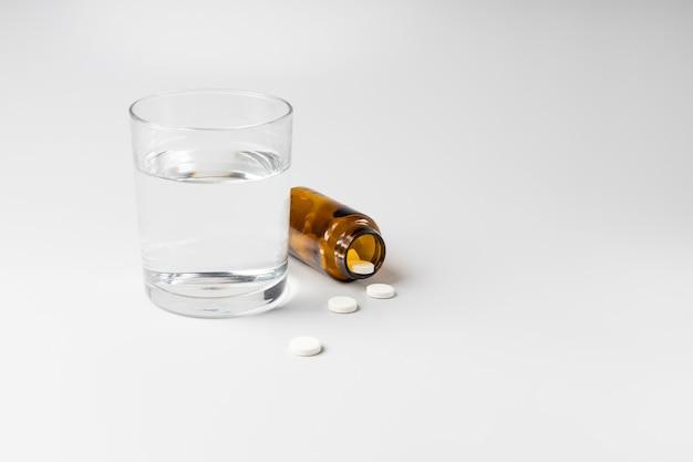 Стакан воды и таблетки из банки на белом фоне