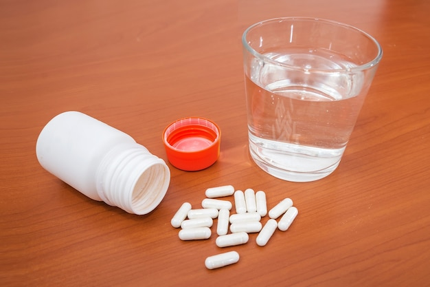 물과 나무 테이블에 약의 유리. 건강 개념입니다.
