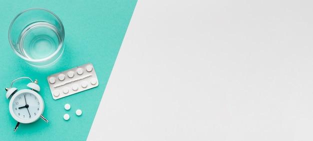 Стакан воды и таблетки на столе
