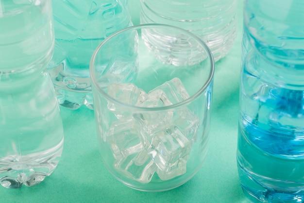Стакан воды и пластиковые бутылки высокий вид