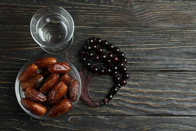 ガラスの水、ナツメヤシのボウル、木製のテーブルの上の数珠