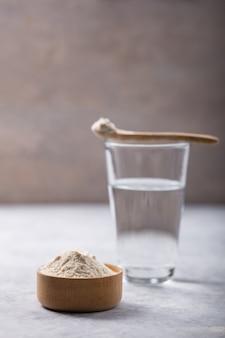 ガラスの水、白いテーブルの上のコラーゲンパウダー。健康的なライフスタイルのコンセプトです。コピースペース