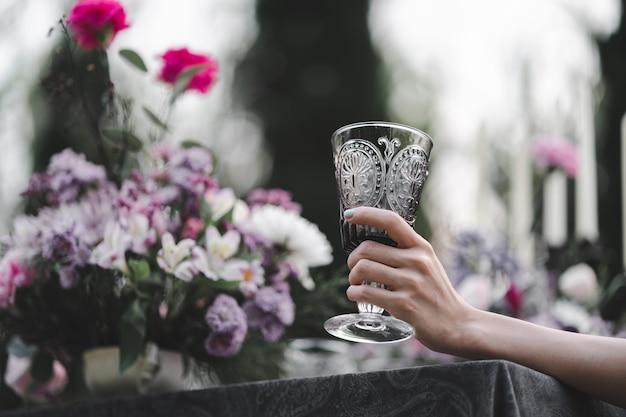 女性の手に水のガラス。庭と花の背景。