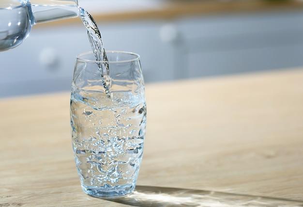 Стакан воды наливается из кувшина в единственный стакан на кухонном столе.