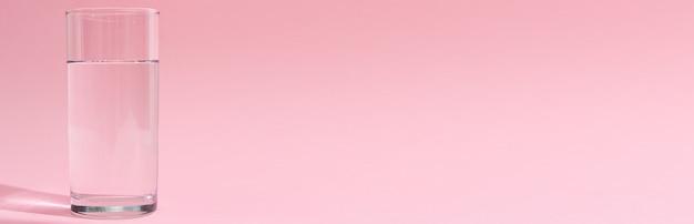 ピンクの背景に水のガラス、長いバナー