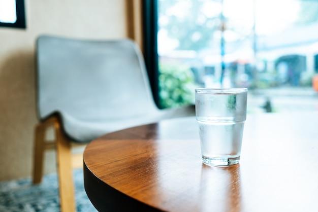 木製のテーブルの上の水のガラス