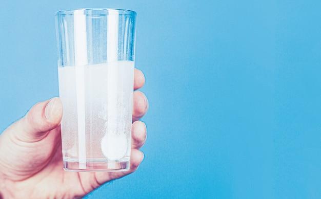 水の錠剤のガラス。泡のある水に発泡錠を入れたガラス。男の手に白い錠剤とコップ1杯の水。健康の概念。錠剤を持っている男のクローズアップ。