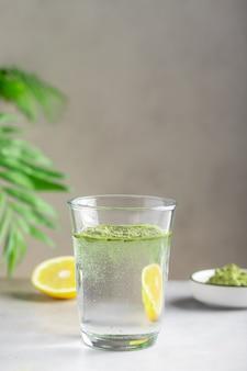 緑のスーパーフードパウダーと水のガラス。健康ドリンク