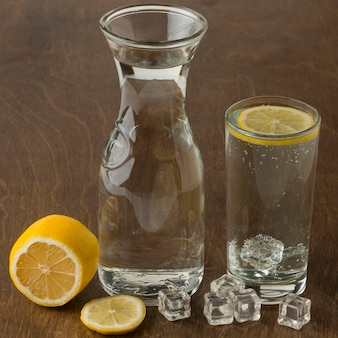 Стакан воды со здоровым ломтиком лимона высокий вид