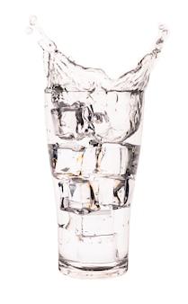 白い表面上に分離されて氷で水の入ったグラス