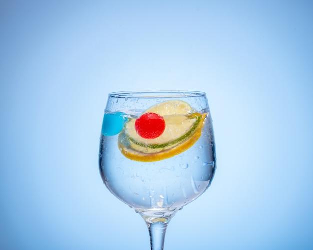 Стакан воды с лимоном и цветными ледяными шариками на голубом фоне градиента.