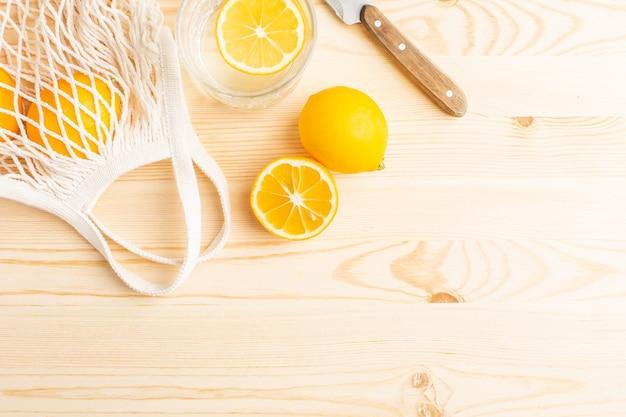 木製のテーブルにレモンと水のガラス、健康的なライフスタイルのための朝の飲み物