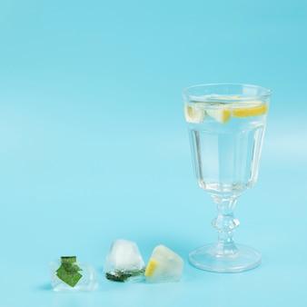 青の背景にレモンと水のガラス