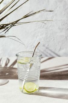 테이블에 레몬 조각과 물 한잔