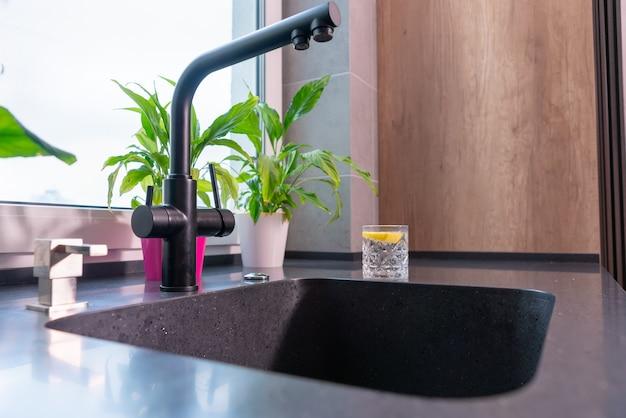 Стакан воды с лимоном стоит на прилавке рядом с кухонной раковиной с современным смесителем и зелеными листьями комнатными растениями в горшках