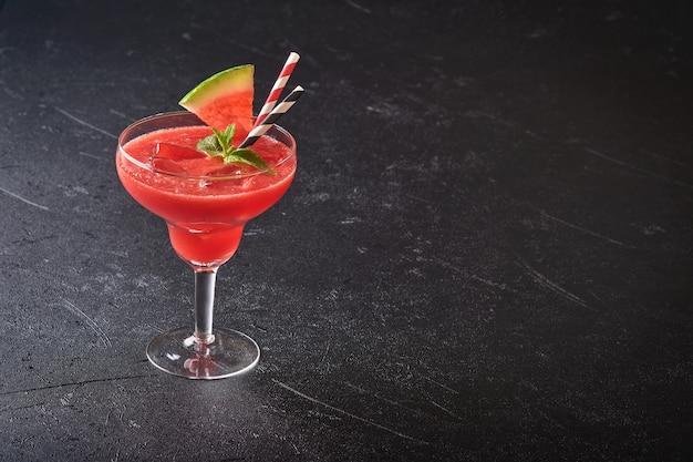 민트와 얼음을 곁들인 수박 마가리타 칵테일 한 잔. 검은 테이블에 안경에 여름 상쾌한 음료. 건강한 여름 식사의 개념입니다.