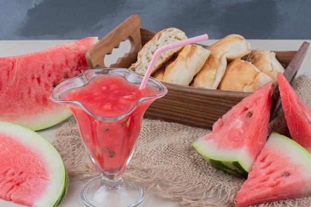 白いテーブルの上のスイカのスムージーとパンのバスケットのガラス。